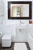White subway tiles in small bathroom; mirror with black vintage frame