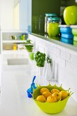Shades of blue and green in wall cabinet and on sink unit of white kitchen counter