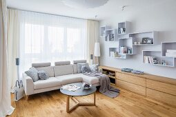 Pale couch and coffee table in front of window, fitted sideboard and shelving modules on wall