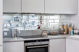 Splashback of mirrored tiles between wall units and hob in fitted kitchen