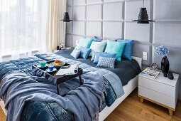 Breakfast tray on double bed with scatter cushions and blankets in shades of blue; pale grey back wall with panelled structure
