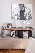 Modern artwork above short, floating shelf and small hifi on sideboard