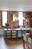 Row of lights above island counter with ample storage space and kitchen counter against brick wall