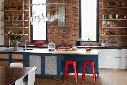 Red metal stools at island counter with ample storage space; kitchen counter against brick wall