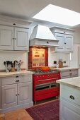Country-house-style, fitted kitchen painted pale grey with red gas cooker under extractor hood and skylight