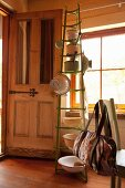Kitchen utensils hung on green bottle rack in rustic kitchen