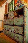 Vintage tins on top of small, rustic chest of drawers with peeling paint
