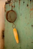 Vintage sieve hanging from wooden cabinet