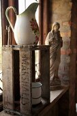 Old washstand pitcher on wooden crate in front of religious statue on windowsill