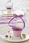 Festive Easter table decoration with hand-crafted paper basket and purple ribbon