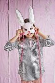 Smiling girl holding hand-crafted rabbit mask