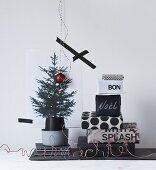 Stapel von verschieden schwarz-weiß eingepackten Geschenken neben Weihnachtsbaumprint
