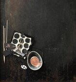 Moodboard in Schwarz-Weiß mit Holzstäbchen, Etiketten, Papier und einer Schale mit Farbe
