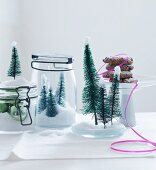 Christmas arrangement of preserving jars filled with artificial snow, baubles and Christmas tree ornaments