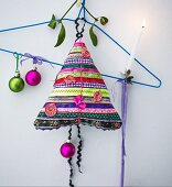Hand-made Christmas-tree-shaped cushion made from colourful strips of fabric