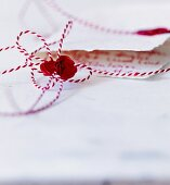 Bow of red and white bakers' twine sealed with sealing wax and stamp of treble clef