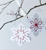 Paper snowflakes with embroidered details and bird ornament on bare branch