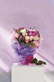 Bouquet of roses, peonies, lavender and sprigs of blackberries lavishly draped in purple tulle