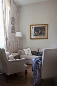 Two classic armchairs and pale grey sofa below gilt-framed engraving