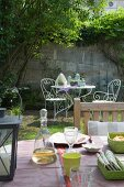 View over set table to ornate, metal garden furniture set