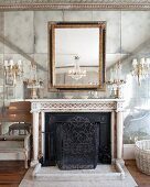 Antique fireplace with chandelier sconces on opulent mirrored wall