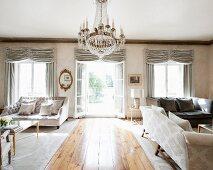 Luxuriöser Wohnraum mit antiken Möbeln, Kronleuchter und bodentiefen Fenstern