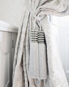 Two elegant, silver tassels on silver curtain