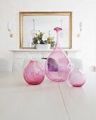 Round, pink glass vases on table in front of mirror above fireplace