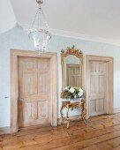 Eingangsbereich mit antiken Möbeln, zwei Kassettentüren und altem Dielenboden