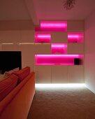 Pink beleuchtete Regalwand hinter einem orangefarbenem Sofa im dunklen Raum