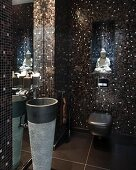 Guest toilet with elegant, shimmering, brown and black mosaic tiles, Buddha figurine and pedestal sink