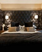 Masculine bed with black upholstered headboard, sconce lamps and dark scatter cushions
