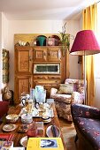 Cluttered coffee table and carved wooden cabinet in eclectic living room