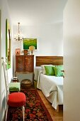 Hand-crafted cabinet next to bed in eclectic bedroom