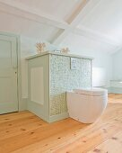 Modern toilet mounted on custom, half-height cabinet covered in pastel-green mosaic tiles