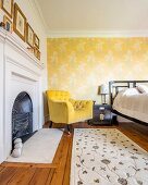 Fireplace, yellow armchair and wallpaper with floral pattern on yellow background in bedroom