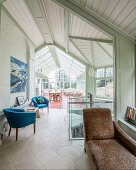 Brown chaise, blue fifties' armchairs in room leading into conservatory