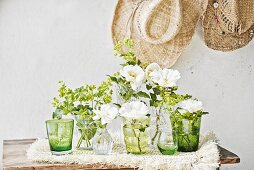 Lady's mantle & white garden roses in various glasses & vases