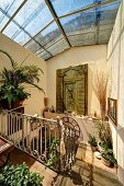 Mediterranean-style, sunny stairwell with glass roof, potted plants on floor and surfaces