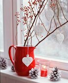 Branches of miniature rose hips and china love-hearts in red jug on windowsill