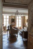 Blick in eleganten Wohnraum im französischen Stil mit Antikmöbeln und Kronleuchter
