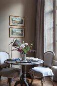 Sitzecke am Fenster mit antiken Polsterstühlen und rundem Holztisch