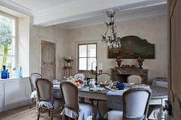 Länglich ovaler Esstisch mit antiken Polsterstühlen in ländlich stilvollem Essraum