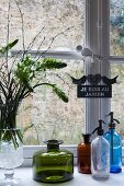Vase of flowers, vintage glass bottles and soda siphon bottles on sill of lattice window