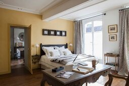Bedroom with yellow walls, double bed and antique desk