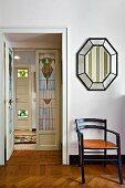 Chair below mirror; view of interior door with art nouveau glass panels in hallway