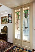 Double doors with art nouveau, stained glass panels in traditional interior