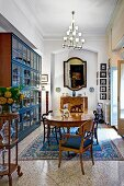 Antique chairs and table on patterned rug, glass-fronted cabinet with blue-painted frame and pendant lamp with small glass lampshades in traditional interior