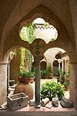 View through arcades into courtyard with potted plants on floor at Villa Cimbrone in Italy