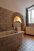 Rustic bathroom with old archway and cement tiles
